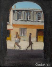 A bright street scene through an archway with walking figures