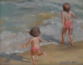 2 little girls in matching swimsuits play at the beach