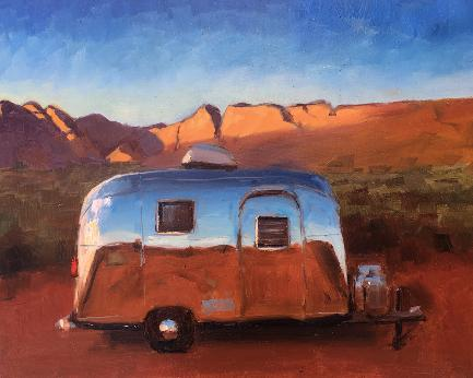 Vintage airstream next to red cliffs in late afternoon light