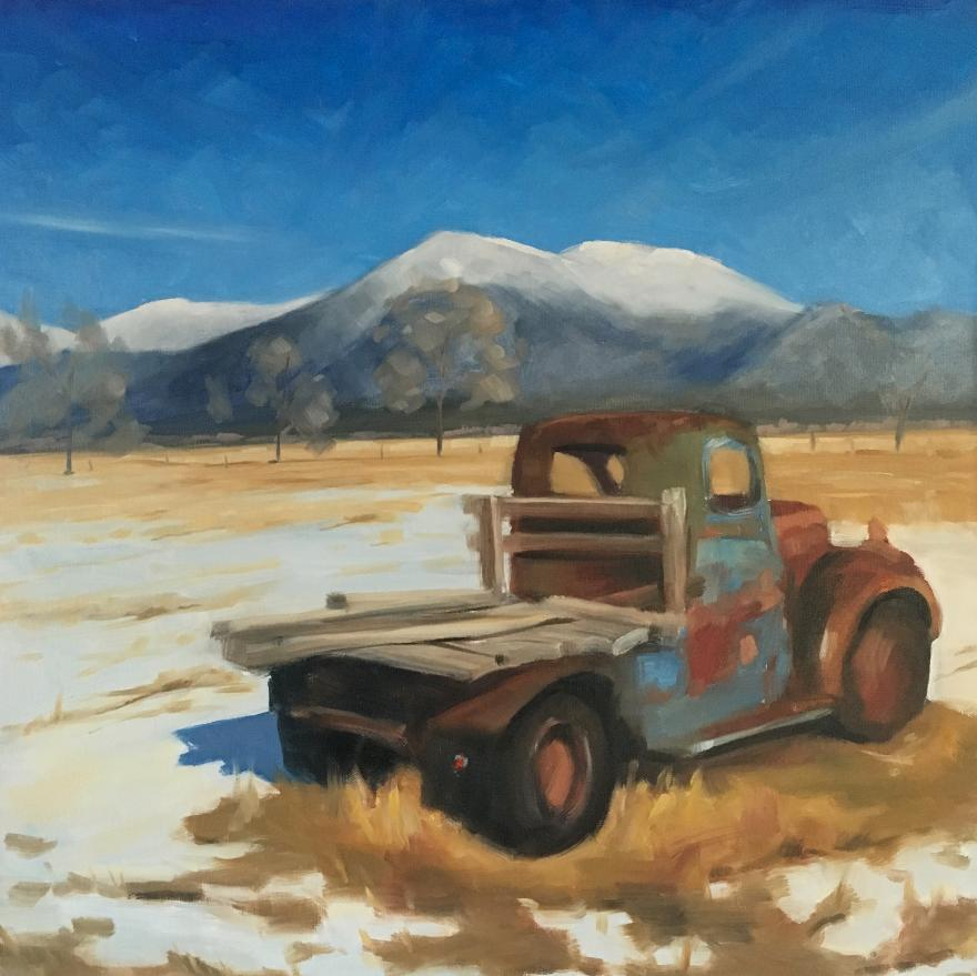 old truck in a paddock with snow mountains