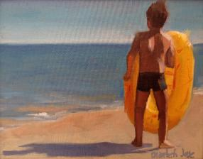 boy with yellow plastic dinghy contemplates the ocean from the beach